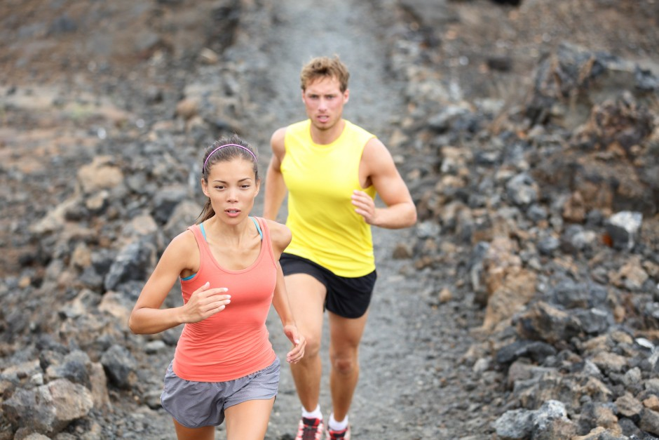 Runners couple running on trail in cross country run outdoors training on Hawaii, Big Island for marathon or triathlon. Fit young fitness model man and asian woman training together outside.