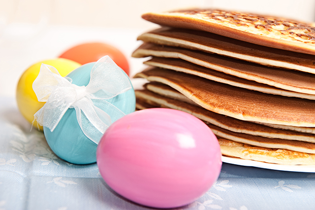 Easter eggs and stack of pancakes with tea and honey