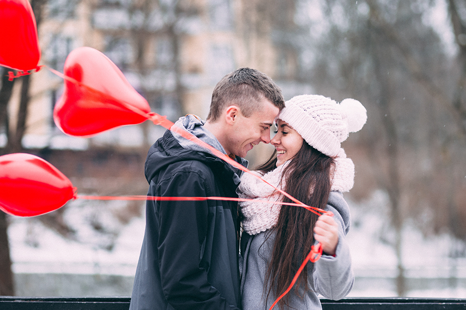 Couple kissing with heart-shaped balloons on Valentine's Day